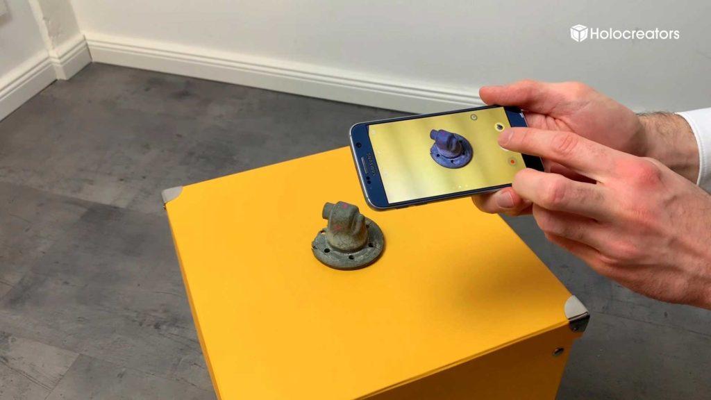 Ein Metallteil wird mit einem Handy für die Photogrammetrie fotografiert.