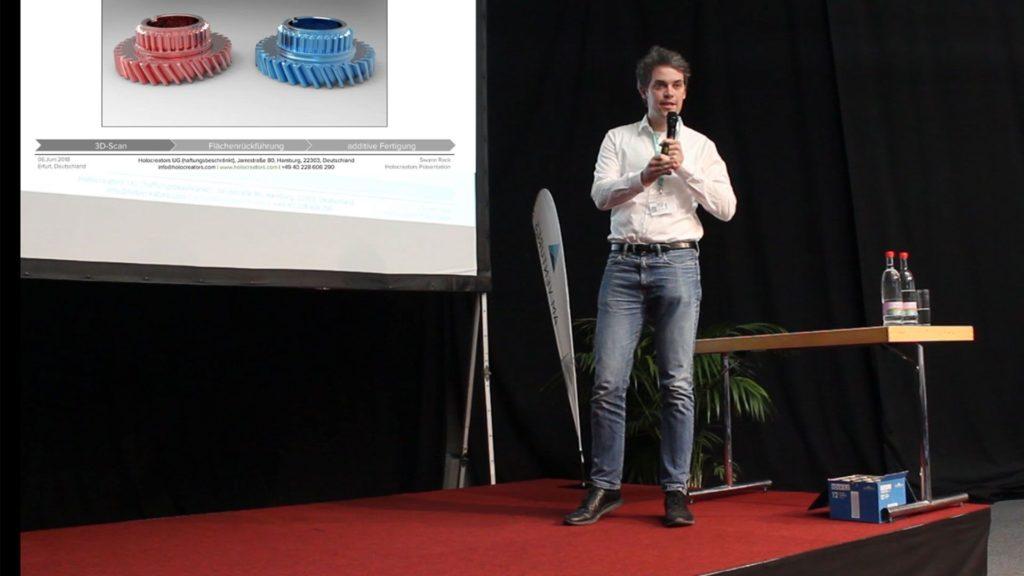 Swann Rack steht mit Präsentationsfolien auf der Bühne der Fabcon Rapid.Tech.