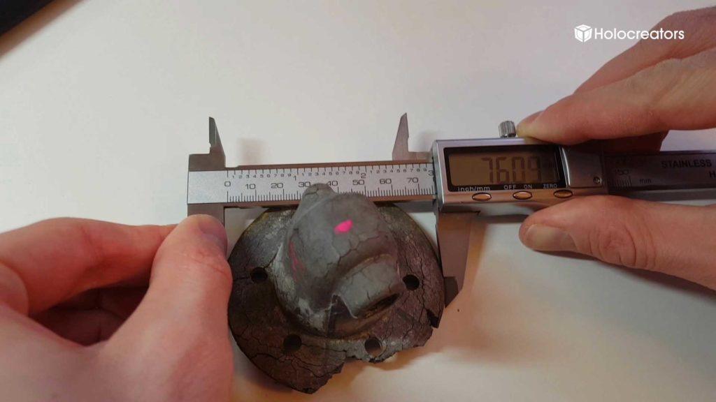 Ein Bauteil wird mit einem Messschieber vermessen.