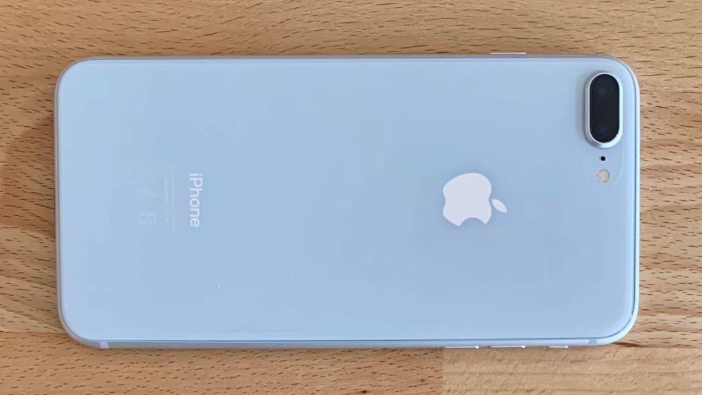 Ein iPhone 8 plus liegt auf einem Holztisch, die Kamera ist nach oben ausgerichtet.